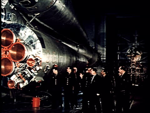 Yuri Gagarin and other future spacemen stand in front of the Vostok 1 rocket