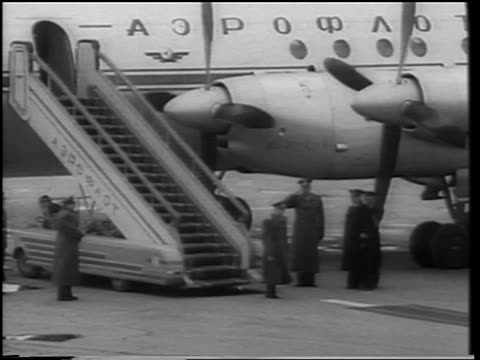 Yuri Gagarin descending stairs from airliner walking on carpet