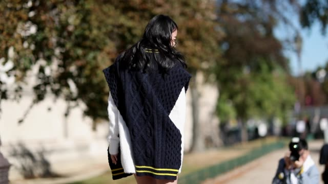 vídeos de stock, filmes e b-roll de yuwei zhangzou wearing navy sleeveless knit with slit white knit worn as dress asymmetric white sneakers is seen outside maison margiela during paris... - cardigan blusa