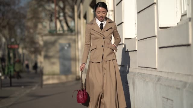 Yuwei Zhangzou wears a beige trench coat a white shirt a tie a pleated dress a red bag outside Dior during Paris Fashion Week Haute Couture Spring...