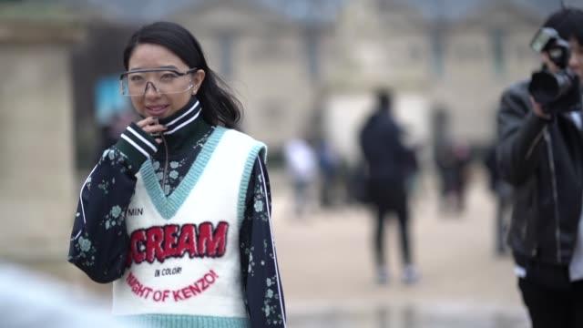 Yuwei Zhangzou wears a floral print dark blue bomber jacket a wool top Scream Night of Kenzo green boots outside Kenzo during Paris Fashion Week...