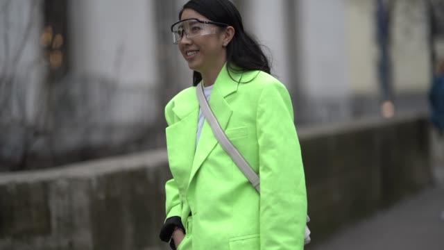 Yuwei Zhangzou wears a neon green/yellow blazer jacket suit pants sneakers shoes sunglasses a white bag outside Acne during Paris Fashion Week...