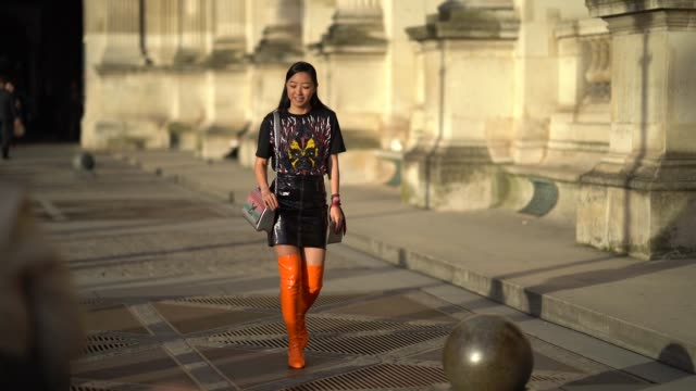 Yuwei Zhangzou wears a orange thigh high boots a print top black leather skirt a bag outside Louis Vuitton during Paris Fashion Week Womenswear...