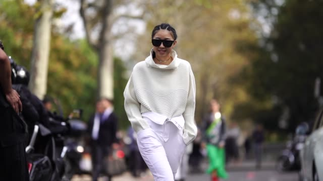 vídeos de stock e filmes b-roll de yuwei zhangzou wears a white wool pullover, white pants, outside issey miyake, during paris fashion week womenswear spring/summer 2019, on september... - camisola