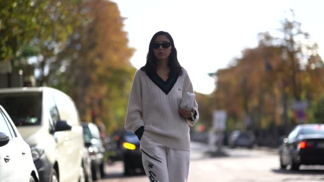 yuwei zhangzou wears sunglasses a lacoste vneck wool pullover a bag white pants outside lacoste during paris fashion week womenswear spring summer... - modewoche stock-videos und b-roll-filmmaterial