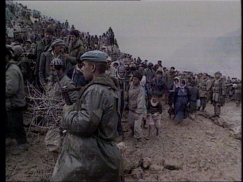 vídeos de stock, filmes e b-roll de zagros mountains ext gvs iraqi soldiers holding back kurdish refugees gathered on mountainside to stop them entering iraq cf = d0616236 or d0616235... - curdo