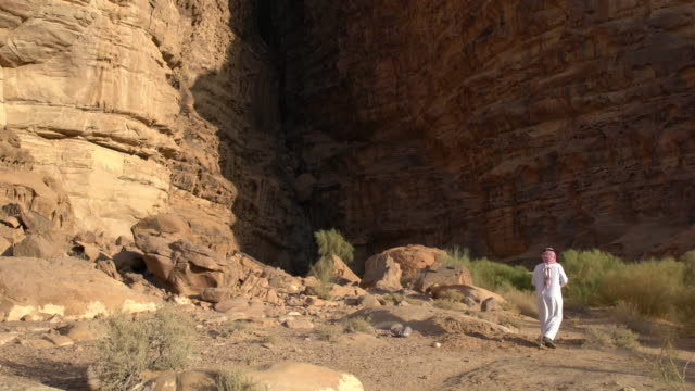Zalabia Bedouin approaching a very steep rock formation in Wadi Rum Desert, Jordan