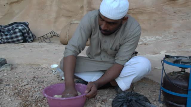 zalabia bedouin preparing traditional arabic bread in  wadi rum desert, jordan - wasserflasche stock-videos und b-roll-filmmaterial