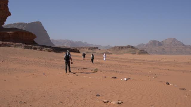 zalabia bedouin tour leader leading a group of tourists in wadi rum desert, jordan - sandstone stock videos & royalty-free footage