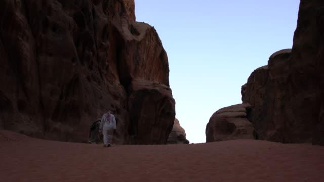 Zalabia Bedouin wearing traditional Arabic clothing approaching a canyon in Wadi Rum Desert, Jordan