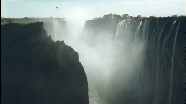 zambezi river gushes over victoria falls with hot air balloon in distance available in hd. - victoria falls stock videos and b-roll footage