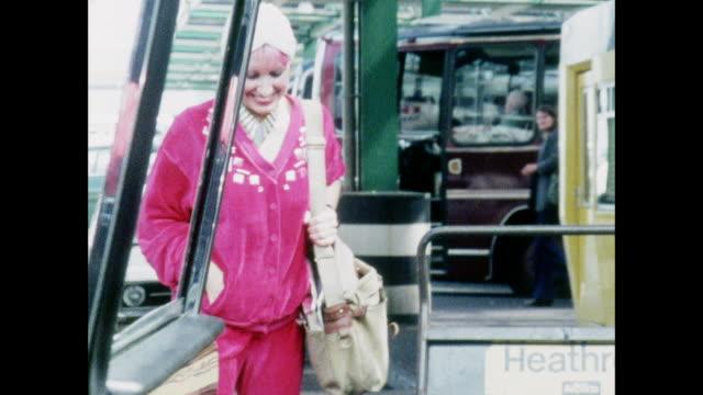 stockvideo's en b-roll-footage met ts zandra rhodes discusses her design empire / uk / zandra rhodes walks across the street and waves / hand opens car door / zandra rhodes gets in car... - passagiersstoel