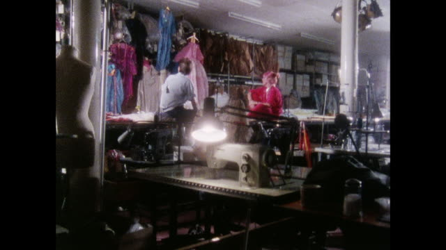 stockvideo's en b-roll-footage met zandra rhodes discusses her empire in her design studio / uk / zandra rhodes and a friend sit on tables and talk / sewing machines fill studio floor - designatelier