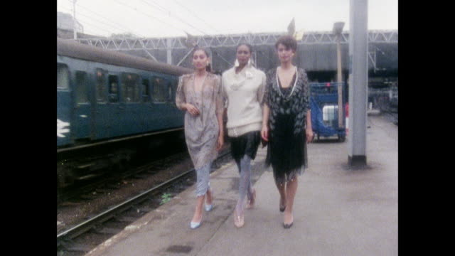 TS Zandra Rhodes dress collection at a railway station / UK / Train rolls by models in dresses / train rolls by models in dresses and blouses / model...
