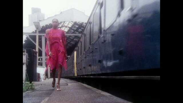 Zandra Rhodes dress collection at train station / UK / Model looks out of train car window / train rolls behind model in dress / models walk at train...