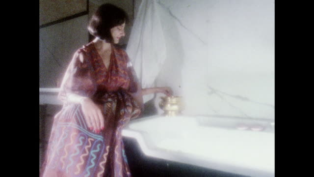 Zandra Rhodes dresses shown in romantic scenes / UK / Model sprays perfume in bathroom / model adds bath salts to tub / woman talks / model walks...