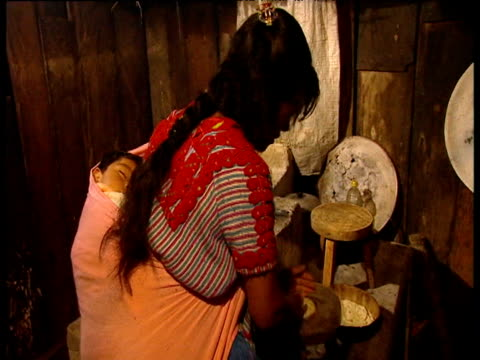 zapatista woman prepares and bakes tortillas while her child sleeps in carrying shawl on her back chiapas region mexico - shawl stock videos & royalty-free footage