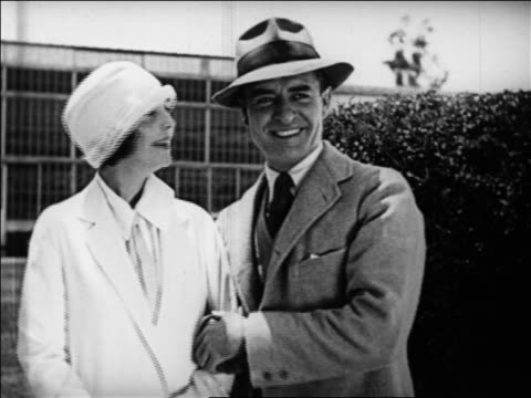 b/w 1925 zasu pitts + john gilbert smiling outdoors + looking off screen / documentary - anno 1925 video stock e b–roll
