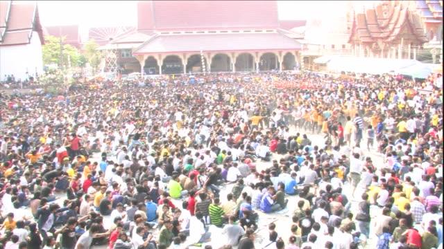 zealous buddhists run through a crowd of worshipers near a buddhist temple in thailand. - acqua santa video stock e b–roll