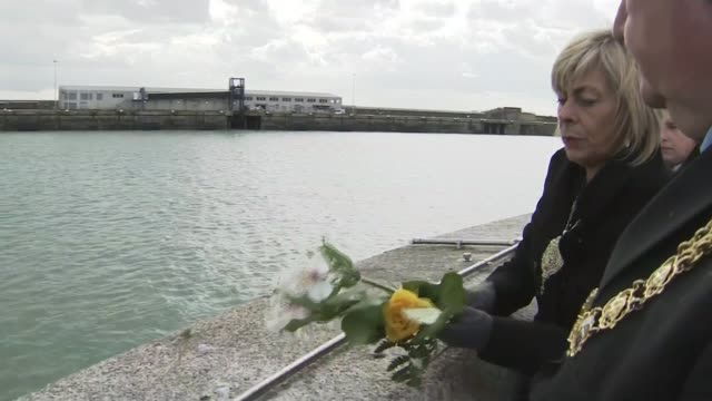 stockvideo's en b-roll-footage met zeebrugge ferry disaster 30th anniversary memorial services held woman throwing flowers into sea from pier people on pier two ferries at sea - zeebrugge