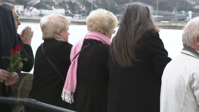 stockvideo's en b-roll-footage met zeebrugge ferry disaster 30th anniversary memorial services held people holding flowers and looking over side of pier man throwing flowers into sea... - zeebrugge