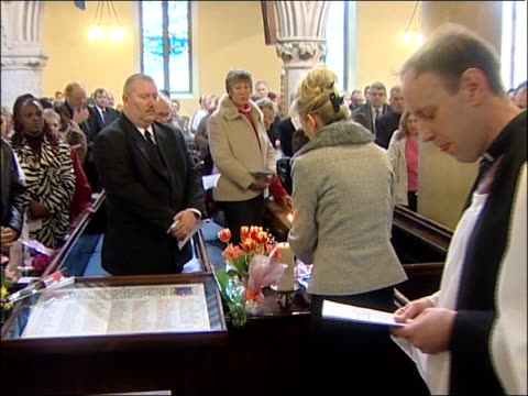 stockvideo's en b-roll-footage met church memorial service held england dover st mary's church int woman lighting a candle at memorial service for 1987 zeebrugge ferry disaster zoom in - zeebrugge