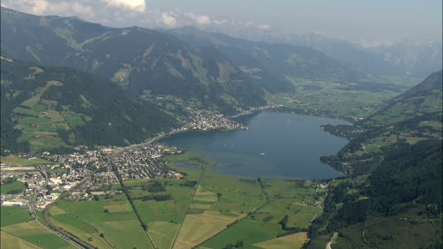aerial zeller see lake surrounded with mountains / zell am see, salzburg, austria - 北チロル点の映像素材/bロール