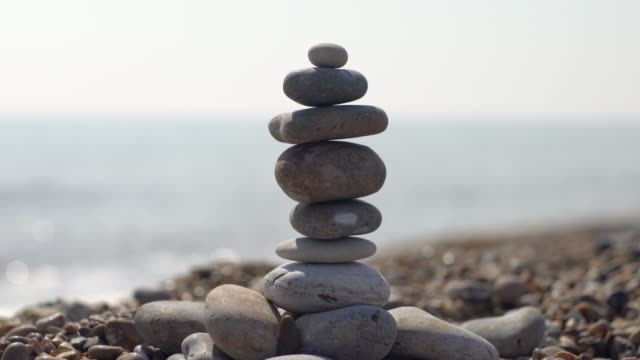 zen like pebbles balanced together on the beach - buddhismus stock-videos und b-roll-filmmaterial