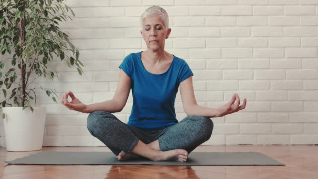 zen-like mature woman practicing yoga in lotus position. - zen like stock videos & royalty-free footage