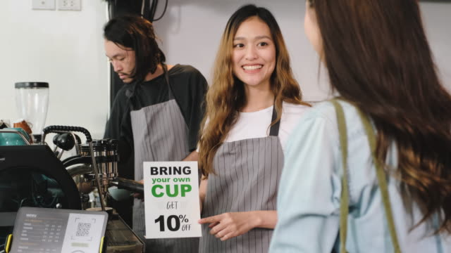 zero waste lifestyle concept.asian barista guidance customer if bring own cup discount 10% off at counter bar in cafe - reusable stock videos & royalty-free footage