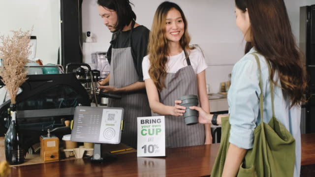 zero waste lifestyle concept.asian bring own cup to buy coffee and giving to barista on counter bar at cafe - carrying stock videos & royalty-free footage
