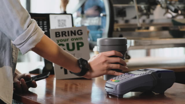 zero waste lifestyle concept.close up hand of asian woman customer bring own cup to buy coffee and pay contactless with mobile phone to barista on counter bar at cafe - cup stock videos & royalty-free footage