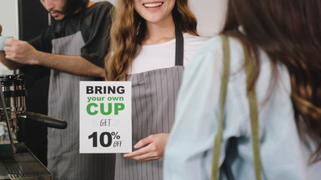zero waste lifestyle concept.slow motion close up asian barista guidance customer if bring own cup discount 10% off at counter bar in cafe - reusable stock videos & royalty-free footage