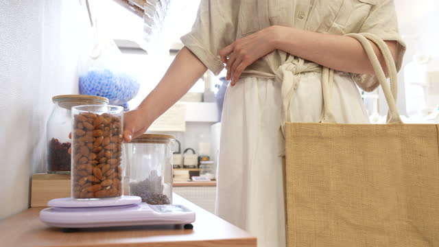 zero waste - young woman customer weighing nuts in glass bottle on scale - three quarter length stock videos & royalty-free footage