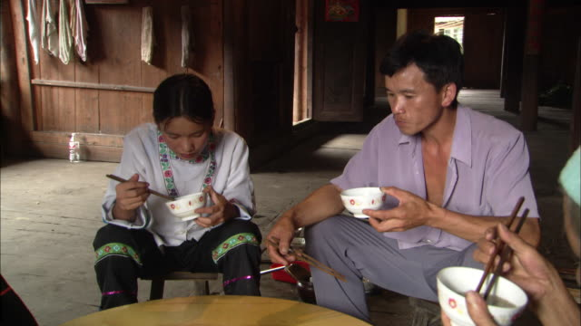Zhuang family sit around table eating from bowls with chopsticks, Ping'an village, Guilin, Guangxi Zhuang