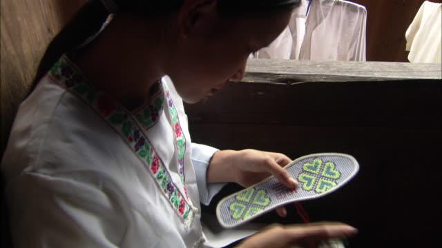 zhuang girl embroidering sole of shoe, ping'an village, guilin, guangxi zhuang - endast en tonårsflicka bildbanksvideor och videomaterial från bakom kulisserna