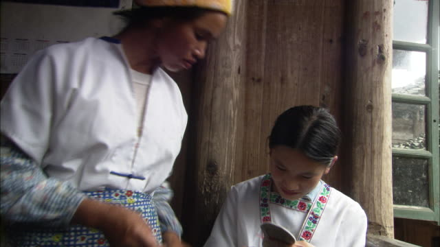 zhuang woman advises as she watches her daughter embroidering on balcony of house. - embroidery stock videos & royalty-free footage