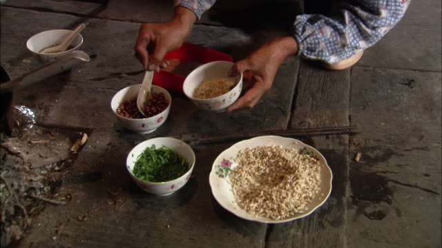 zhuang woman spoons rice, peanuts and herbs into bowl then adds chilli liquor, ping'an village, guilin, guangxi zhuang - halten stock-videos und b-roll-filmmaterial