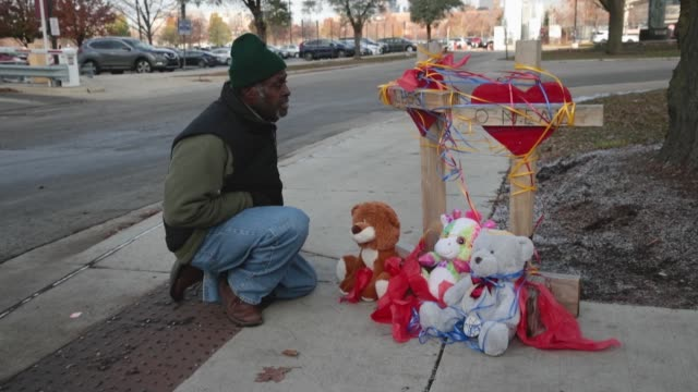 Ziff Sistrunk of crosses for the Losses sings after placing crosses outside of Mercy Hospital where four people were shot and killed yesterday on...