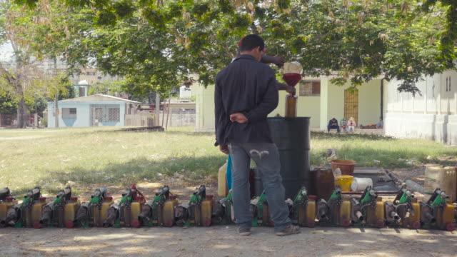 Zika virus extermination campaign in Cuba. Fumigatio against aedes mosquito. 2 men working on the extermination equipment. Cuban flag on the background.
