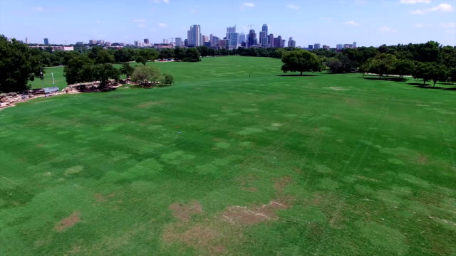 Zilker Park Aerial view over green grass field with Town Lake Skyline Cityscape in the Background low angle