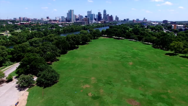 Zilker Park Aerial view over green grass field with Town Lake Skyline Cityscape in the Background High Angle