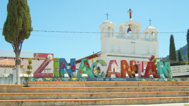 vídeos de stock e filmes b-roll de zinacantan, chiapas, mexico multi-colored banner in front of a church - chiapas
