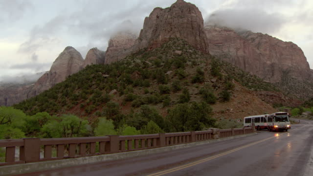 Zion National Park shuttle bus passing camera with wet road and clearing storm