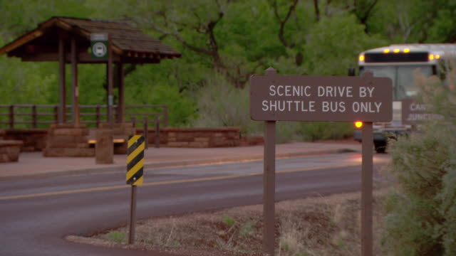 Zion National Park shuttle bus stopping in front of sign that says SCENIC DRIVE BY SHUTTLE BUS ONLY