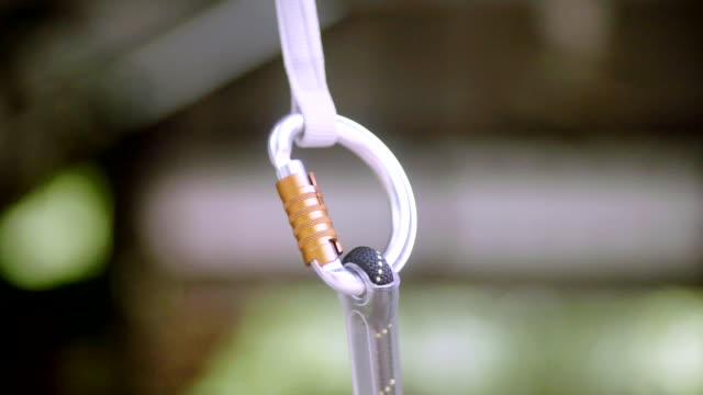 zipline carabiner equipment for ziplining and climbing in the adventure park. - climbing equipment stock videos and b-roll footage