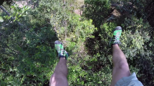 pov ziplines past tree tops in belize - human leg stock videos & royalty-free footage