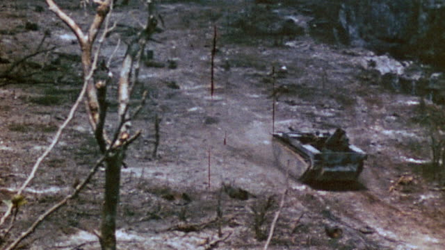zippo flamethrower tank advancing and spewing flames at hillside and brush burning / iwo jima japan - schlacht um iwojima stock-videos und b-roll-filmmaterial