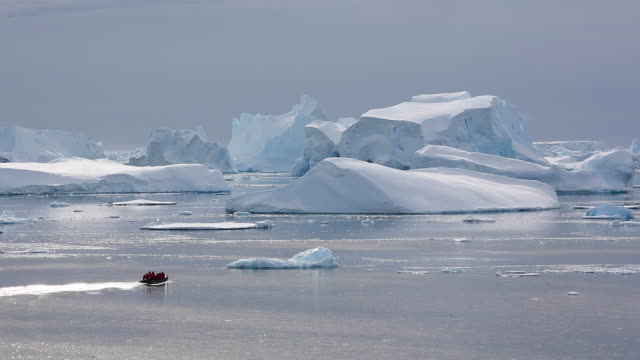 Zodiac with tourists moving across an iceberg landscape in Antarctica