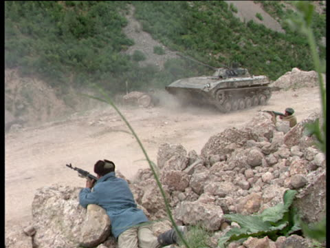 zoom and pan as soldiers and tank fire guns into mountainside during tajikistan civil war tajikistan 1992 - caterpillar track stock videos and b-roll footage